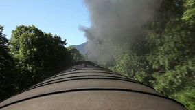 The train`s roof while it is moving smoke is rising. Shot of the train`s roof while it is moving. Smoke is rising from the locomotive`s chimney stock video footage