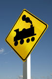 Train sign. Warning sign for approaching train tracks on blue background Royalty Free Stock Photos