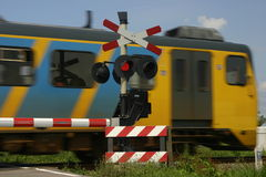 Train and signals. Yellow and blue train passes in high speed a red signal on a crossover Royalty Free Stock Photos