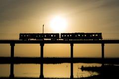 Train silhouette. The trains run on the bridge at dawn Royalty Free Stock Photo
