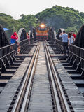 A train slowly crosses the famous bridge over the river kwai in. Kanchanaburi, Thailand Royalty Free Stock Images