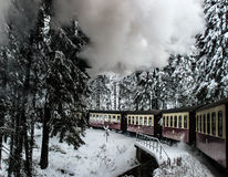 Train in the snowy forest over bridge. Dramatic winterlandscape with smoke, german Harz mountains Stock Photo