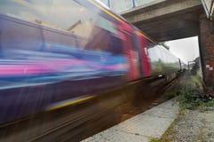 Train speeding in blur under bridge Royalty Free Stock Image