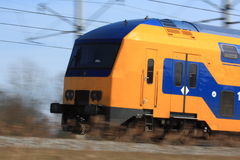 Train speeding by. Close-up of a Dutch doubledecker train speeding by (motion blur Royalty Free Stock Photography