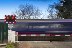 Train speeding through a level crossing Stock Photography