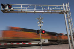 Train speeding by railroad crossing royalty free stock images