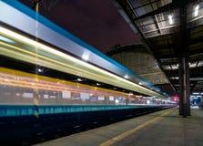 Train speeding through railway station with extended motion. Stock Photos