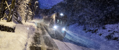 Train speeding in a snowy winter night Stock Image