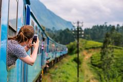 Train in Sri Lanka. Young woman enjoying train ride from Ella  to Kandy among tea plantations in the highlands of Sri Lanka Stock Photo