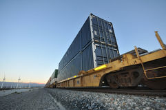 Train with stacked containers rolls by windfarm Stock Images