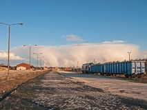 An impending cataclysm. Train standing on the siding, railway tracks, railway station in the distance. In the distance, on the horizon you can see a boiling royalty free stock image