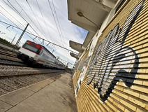 Train Station. Train arrival to a train station. Perspective taken in order to give a dynamic character to the scene, highlighting the graffiti on the walls Stock Image
