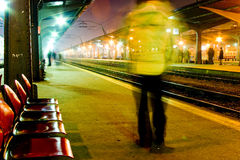 Train station. At night, photographed showing illumination of lights and movement of passenger.  Motion blur visible with person walking past the camera Stock Photo