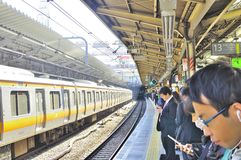 At the train station. People busy reading their handphone messages and books while lining up in several queues , waiting for the train to arrive at the Akihabara Stock Photos