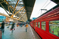 Train station. With red train and  blurred people Stock Image