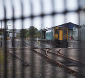 Train at station behind railings. A train stopped in Carmarthen Railway station, Carmarthenshire, South West Wales.  Taken through out of focus railings Royalty Free Stock Images