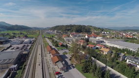 Train station in the countryside. Helicopter camera flaying above the train station in the middle of a countryside on a sunny day stock video