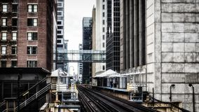 Train Station on Elevated tracks within buildings at the Loop, Glass and Steel bridge between buildings Chicago City Center -  Ble. Ached Portrait Artistic Stock Images