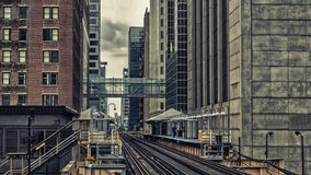Train Station on Elevated tracks within buildings at the Loop, Glass and Steel bridge between buildings Chicago City Center - Dar. Train Station on Elevated Royalty Free Stock Images