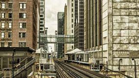 Train Station on Elevated tracks within buildings at the Loop, Glass and Steel bridge between buildings Chicago City Center - Dark. Gold Artistic Effect Royalty Free Stock Image