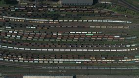 Train station with freight trains and containers in aerial view. Aerial shooting top down footage of railway. Transportation hub showing the different trains stock video
