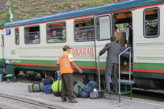 Train station officers loading tourists luggages into Inca Rail Stock Photo