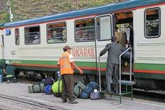 Train station officers loading tourists luggages into Inca Rail. Ollantaytambo Peru - April 23 2014: Train station officers loading tourists luggages into Inca stock photo