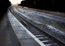 Train Station Platform. Desolate, sheltered train station platform with twin and single rail tracks stock photos