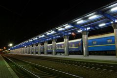 Train Station Platform in the Night. Empty rail road station in the night, Blue train's wagons is standing behind metal platform Royalty Free Stock Photography