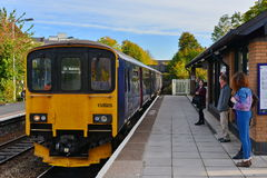 Train Station Platform View. TROWBRIDGE, UK - OCTOBER 20, 2015: Rail passengers wait on a station platform for an approaching train. Opened in 1848 the station Stock Images