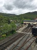 A train station beside a river in wales. A train station right next to the river in the hills in wales stock photo