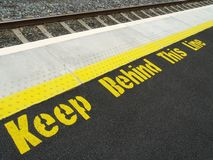 Train Station Safety. A warning sign on a train station platform Royalty Free Stock Photos