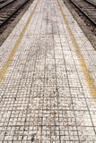 Train station sidewalk. With yellow lines and square tiles Royalty Free Stock Photo