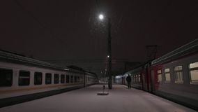 Train station at snowy night. Lonely human figure walking on platform and going into the railway wagon. Local train station at snowy night. Lonely human figure stock video footage