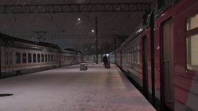 Train station at snowy night. Lonely human figure walking on platform. Local train station at snowy night. Lonely human figure walking on platform stock video footage