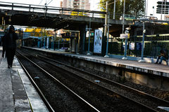 Train station with some people waiting at dawn. A Train station with some people waiting for commute royalty free stock image