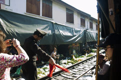 Train station staff pulldown rail level crossing barriers on road. While train arrival at Mae klong Railway Market on April 12, 2017 in Samut Songkhram Royalty Free Stock Images