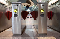Train Station Turnstiles. Turnstiles in underground railway station. Green arrows pointing to the way forwards. Red barriers preventing progress royalty free stock photos