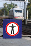 Train station warning 2. A warning-sign at a german train station, in the background an ice speed train Stock Photo