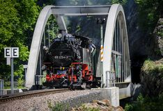 Train with a steam engine going over a bridge royalty free stock images