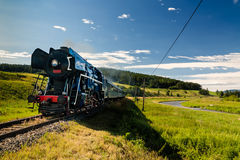 Train with a steam locomotive. Steam engine locomotive train moving next to the river Stock Image