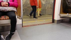 Train stop on subway station. Opening doors in carriage of subway train. stock video footage