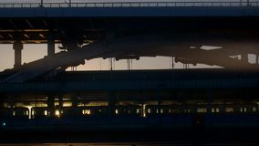 The train stops at the metro station, by the rays of the setting sun. The train stops at the metro station, on the bridge illuminated by the rays of the setting stock footage