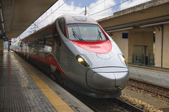 The train stops near the platform station in Italy. The train stops near the platform at railway station in Italy Stock Photos