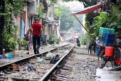 Train street, Hanoi, Vietnam. Train tracks running between homes in Hanoi, Vietnam, with rubbish, people and trees Stock Photography