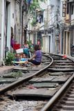 Train street, Hanoi, Vietnam. Woman and children sitting by side of railway tracks in Train Street, Hanoi, Vietnam Stock Image
