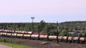 Train with tanks near forest and village stock footage