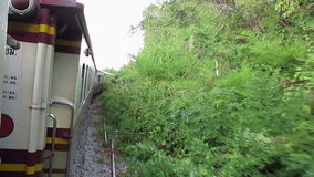 Train, Thailand Burma Railway. Train ride on the Japanese built Burma and Thailand line during World War II or WWII. The line was made famous by the movie Bridge stock video