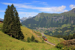 Train to Muerren with mountains and Wengen at the background. View at the train from Gruetschalp to Muerren in Switzerland. Mountain landscape with the village Royalty Free Stock Images