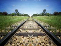 Train track to sky on green grass wood field royalty free stock photography